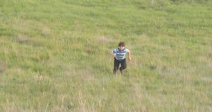 El muchacho corre a través del campo con la hierba verde almacen de metraje de vídeo