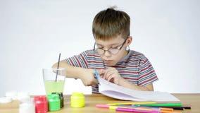El muchacho corta el papel con las tijeras almacen de metraje de vídeo