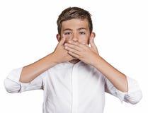 El muchacho, cubriendo su boca con las manos no hablará No hable ningún mal Imagen de archivo libre de regalías