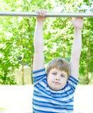 El muchacho cuelga en una barra horizontal foto de archivo