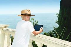 El muchacho cuesta contra la perspectiva del mar y de usar la tableta Foto de archivo
