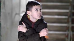 El muchacho cuidadoso curioso congelado camina a una casa vieja dilapidada fotografía de archivo