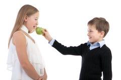El muchacho da a la muchacha una manzana Imagen de archivo libre de regalías