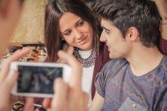 El muchacho da llevar las fotos los pares adolescentes en el sofá Imagenes de archivo