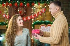 El muchacho da a muchacha la caja rosada con en forma de corazón el día del ` s de la tarjeta del día de San Valentín Fotografía de archivo