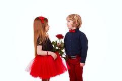 El muchacho da a muchacha un regalo de la rosa imágenes de archivo libres de regalías