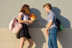 El muchacho da el ramo de la muchacha de flores Retrato al aire libre de los adolescentes de los pares Foto de archivo