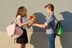 El muchacho da el ramo de la muchacha de flores Retrato al aire libre de los adolescentes de los pares Imagen de archivo libre de regalías