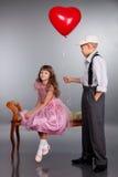 El muchacho da un globo rojo a la muchacha Fotos de archivo