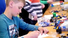 El muchacho de 12 años, dibuja un dibujo, un proyecto de un modelo del robot, una máquina, juegos en el diseñador de los cubos, p metrajes