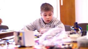 El muchacho de 10 años, dibuja un dibujo, un proyecto de un modelo del robot, una máquina, juegos en el diseñador de los cubos, p almacen de metraje de vídeo