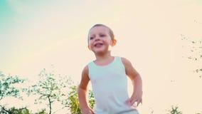 El muchacho de 4 años en una camiseta blanca ríe, niño salta para arriba contra el cielo Retrato de un niño activo alegre en una  almacen de metraje de vídeo