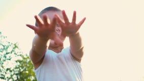 El muchacho de 4 años en una camiseta blanca ríe y estira hacia fuera sus manos Retrato de un niño activo alegre en una naturalez metrajes