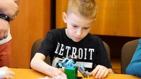 El muchacho de 9 años, juegos en el diseñador de los cubos, placas, circuitos, alambres un pequeño inventor crea los robots, máqu metrajes