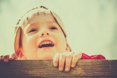 El muchacho de 3 años lindo juega emocionado en una diapositiva amarilla del patio en un día fresco imágenes de archivo libres de regalías