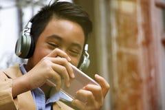 El muchacho de Asain está jugando a juegos del teléfono móvil Imágenes de archivo libres de regalías