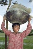 El muchacho de Bangladesh da une vuelta al estirón con la cacerola grande Fotos de archivo libres de regalías