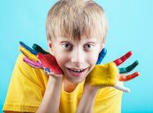 El muchacho de Cheeful en la demostración amarilla de la camiseta pintó las manos Imagenes de archivo