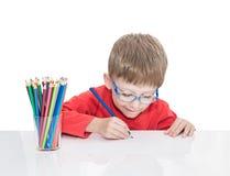 El muchacho de cinco años en puntos azules se sienta en una tabla blanca y y dibuja los lápices Fotografía de archivo libre de regalías