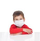 El muchacho de cinco años enfermo se sienta en una tabla blanca con la máscara de la atención sanitaria de la medicina para es vi Foto de archivo