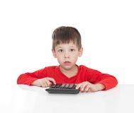 El muchacho de cinco años que se sienta en una tabla blanca y las prensas la calculadora del botón Imagen de archivo libre de regalías