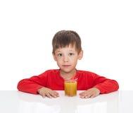 El muchacho de cinco años se sienta en una tabla blanca cerca del zumo de naranja de una paja Foto de archivo