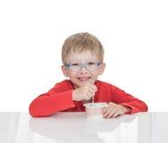 El muchacho de cinco años se sienta en una tabla blanca y come el yogur Fotos de archivo