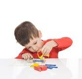 El muchacho de cinco años se sienta en una tabla blanca y juega a un diseñador electrónico Foto de archivo libre de regalías