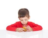 El muchacho de cinco años se sienta en una tabla blanca y un zumo de naranja de consumición Fotografía de archivo libre de regalías
