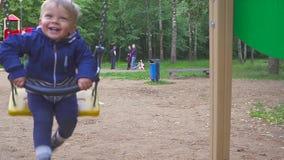 El muchacho de dos años está montando en un oscilación en el parque almacen de metraje de vídeo