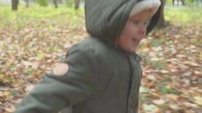 El muchacho de dos años que corre en el bosque del otoño, parquea la cámara lenta almacen de metraje de vídeo