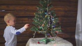 El muchacho de dos años que juega con la Navidad juega en el árbol de navidad, cierre para arriba Retrato de un niño cerca de un  almacen de video