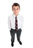 El muchacho de escuela típico se coloca en uniforme Imagen de archivo