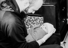 El muchacho de Holds Newborn Baby del padre envolvió en una manta como él mira para arriba su papá Foto negra y blanca fotografía de archivo libre de regalías