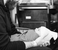 El muchacho de Holds Newborn Baby del padre envolvió en una manta como él mira para arriba su papá Foto negra y blanca fotografía de archivo