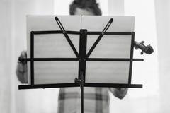 El muchacho de la casa toca un violín Foto de archivo