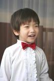 El muchacho de la paginación con rojo arquear-ata la sonrisa Imagen de archivo