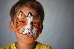El muchacho de los años con los ojos azules hace frente a la pintura de un gato o de un tigre Naranja Fotos de archivo libres de regalías