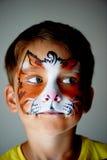 El muchacho de los años con los ojos azules hace frente a la pintura de un gato o de un tigre Naranja Imagenes de archivo