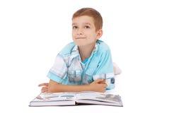El muchacho de los jóvenes soña cerca del libro abierto Imagen de archivo libre de regalías
