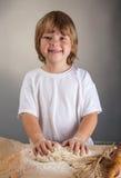 El muchacho de los niños amasa la pasta Imagenes de archivo