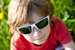 El muchacho de pelo rubio en gafas de sol Fotografía de archivo