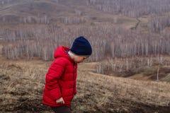 El muchacho de seis años en una chaqueta roja camina fuera de la ciudad en la primavera en las montañas fotografía de archivo libre de regalías