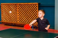 El muchacho de siete años bate la bola en tenis de mesa imagen de archivo