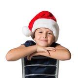 El muchacho de siete años en sombrero rojo sonríe alegre Imagen de archivo