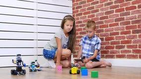 El muchacho de siete años y la muchacha juegan los robots electrónicos, coches, juguetes modernos en el control de radio nuevas t