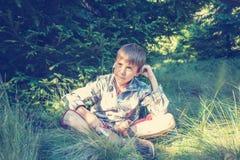 El muchacho de sueño en auriculares se sienta en la hierba enorme Fotografía de archivo