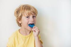 El muchacho de tres años muestra al instructor miofuncional para iluminar el mou Fotos de archivo