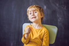 El muchacho de tres años muestra la placa vestibular Placa con una gota a Fotografía de archivo