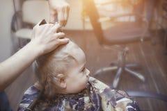 El muchacho de un año hace por primera vez el corte de pelo en una peluquería de caballeros imagenes de archivo